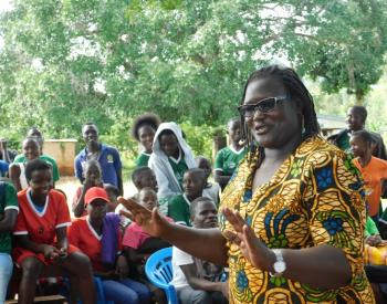 "Easter Okech speaking at ""Sports for change"" SRHR conversations, with a group of people listening in the background."